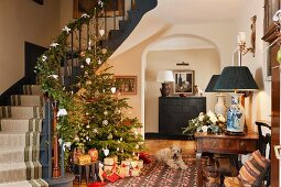 Open-plan foyer of traditional country house with decorated Christmas tree and garland on staircase balustrade