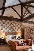 Récamier at foot of double bed against wall with floral wallpaper in rustic attic bedroom