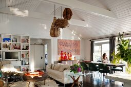 Open-plan interior with vintage ambiance and Long-Island style - lampshades made from natural materials hanging from white wooden ceiling and classic fifties chairs in dining area