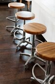 Row of vintage bar stools with round wooden seats on purist steel bases