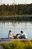 Man, woman and dog sitting on wooden jetty next to lake in evening sun