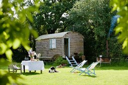 Nostalgic caravan on green lawn with set table and pale blue deckchairs in romantic setting