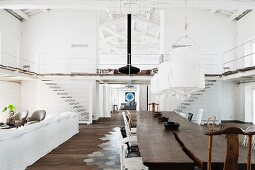 Rustic, solid wood table below pendant lamps with white fabric lampshades opposite lounge area in loft apartment