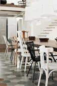 Dining table with various chairs on tiled floor area and pendant lamps with white fabric lamps