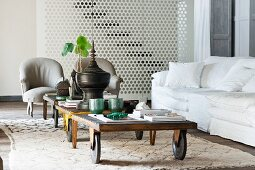 Old luggage carts used as coffee tables on Moroccan rug in front of white couch and grey armchairs