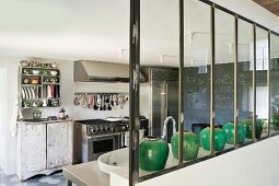 Green ceramic vases on half-height wall in kitchen with vintage cupboard next to stainless steel cooker; blackboard wall in background