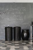 Black recycling bins made from upcycled car tyres against blackboard wall and on honeycomb tiles