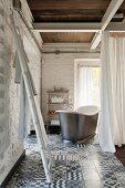 Ladder used as towel rack, vintage bathtub behind curtain in corner of room with whitewashed brick walls and patterned tiled floor