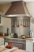 Moderner Elektroherd mit Retroelementen und aufgehängten Kochlöffeln an einer Stange unter der Dunstabzugshaube