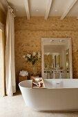 Freistehende Wanne mit Holzablage und Spiegel an Natursteinwand im Bad Ensuite