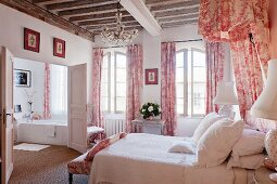 Romantic bedroom with red and white Toile de jouy curtains and bed canopy, rustic wood-beamed ceiling and view into ensuite bathroom in shabby chic atmosphere