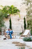 Man reading in wooden deckchair in summery courtyard with high, climber-covered wall of Provençal townhouse