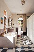 Concrete bathtub opposite white cupboard on chequered floor; open terrace door in background