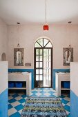 Blue and white chequered floor in bathroom with arched door flanked by twin washstands
