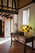 Vase of sunflowers on wooden console table in foyer of country house with terracotta floor