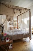 Romantic canopied bed with translucent curtain material in rustic interior