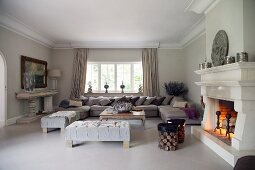 Spacious living room open fireplace, sofa combination and ottomans in traditional ambiance