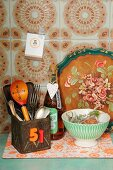 Ethnic wooden spoon in old tin can, bottle of home-made vinegar with decorative tag and drinking bowl on 70's board in front of tray with rustic, floral painted motif; 70's tiles in background