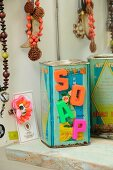 Magnetic letters reading SOAP stuck on old, vintage, metal tea caddy printed with Chinese characters in bathroom