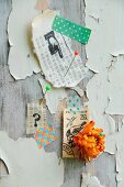 Postage stamps, everlasting flower, printed Oriental paper and washi tape decorating wooden wall with extremely weathered paint