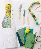 Fabric swatches in shades of green, yellow tulip, string of wooden beads and paint samples on wooden lolly sticks