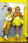 Grauer Teppich mit gelbem Rand; darauf ein Junge und ein Mädchen in Gelbtönen gekleidet
