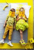In Gelbtönen gekleidete Kinder auf einem grauen Teppich mit gelber Bordüre liegend