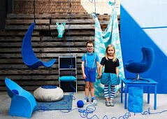 Boy and girl in blue clothing standing amongst furniture for child's bedroom in shades of blue in front of rustic wooden wall