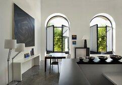 Aufenthaltsraum mit offenen Fenstern, moderner Kunst und Einrichtungsgegenständen (Kunstgalerie Eric Linard, Frankreich)
