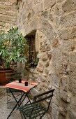 Gartentischchen und zwei Stühle im Innenhof (Kunstgalerie Eric Linard, Frankreich)