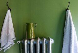 Wandhaken mit Handtüchern & Kanne auf Heizkörper vor grüner Wand