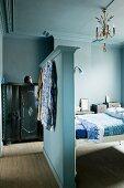 Schlafzimmer in Blautönen mit Bett, Zwischenwand als Kopfteil & antikem Schrank