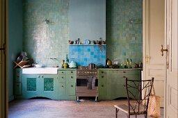Küchenzeile mit grünen Schränken vor grüner Fliesenwand