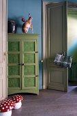 Wohnraum mit blauen Wänden, grünem Schrank, Dekohasen & Dekopilzen