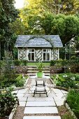 Gardens with symmetrical beds and view of summerhouse with trellising