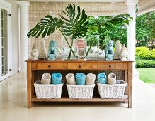 Spa oasis - rolled towels in baskets below rustic wooden console table on veranda of colonial-style villa