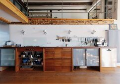 Kitchen counter below gallery with balustrade in open-plan, country-house interior