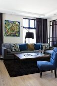 Chair with blue upholstery and turned legs, coffee table in front of sofa and arc lamp in corner of living room
