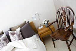 Double bed, modern bedside cabinet in exotic wood and country-house-style armchair on white wooden floor