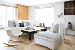Two comfortable chaise sofas with scatter cushions and blankets and classic rocking chair around large wooden table in Scandinavian living room