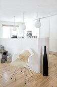 Large, black decorative bottle and classic shell chair with sheepskin rug in front of half-height, masonry wall element and spherical lamps