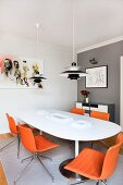Poulsen pendant lamp above white dining table and swivel chairs with orange leather covers in corner with one grey wall