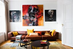 Lounge area with black metal coffee table in front of brown leather sofa below expressive paintings on wall