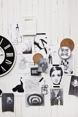 Black and white pictures, fashion sketches and vintage clock on white wood cladding