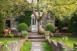 Idyllic cottage with terrace surrounded by garden and brick walls in vintage, artistic ambiance