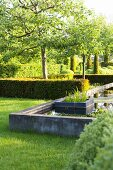 Well-tended landscaped gardens with geometric hedges, trees, lawns and concrete pool