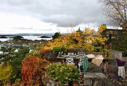 Autumnal terrace with rustic dining table and view across Norwegian skerry coast
