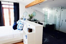 White bedroom with glass shower partition in open-plan bathroom