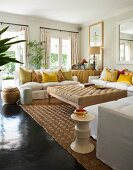 Large ottoman surrounded by white sofas with many yellow scatter cushions in bright living room with dark, glossy floor