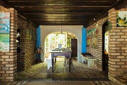 Dining area with colourful religious pictures on brick walls, dark wooden ceiling and rustic wooden furniture